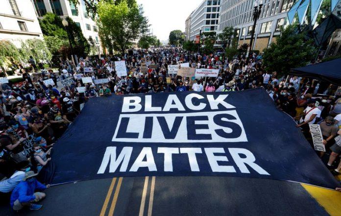 Manifestantes sostienen un cartel gigante en la Plaza Black Lives Matter, cerca de la Casa Blanca, durante una protesta contra la desigualdad racial después de la muerte de George Floyd bajo custodia policial en Mineápolis, en Washington.